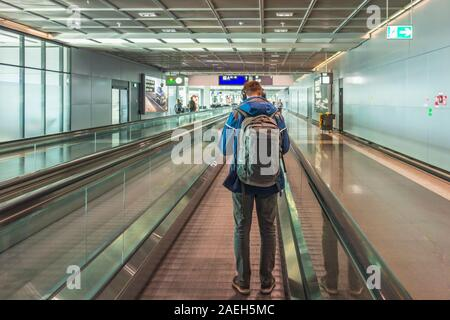 Man standing on a moving walkway at an airport