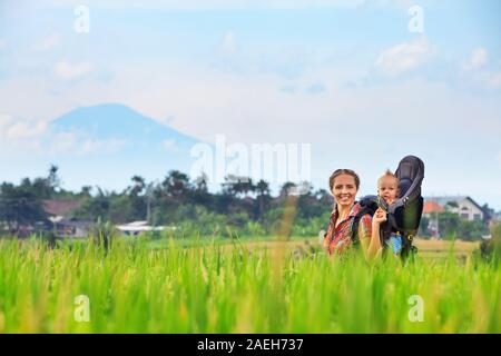 Nature walk in green rice field. Happy mother hold little traveller in carrying backpack. Baby ride on woman back. Travel adventure, hiking with kids - Stock Photo