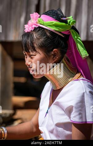 Portrait of a young woman from Kayan tribe wearing traditional outfit (and a modern watch) and brass necklace. Pan Pet, Loikaw, Myanmar.
