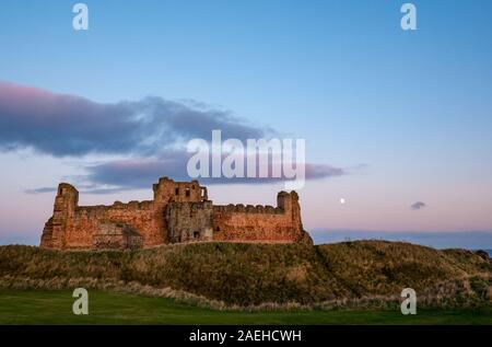 East Lothian, Scotland, United Kingdom, 9th December 2019. UK Weather: A clear sky with a nearly full waxing gibbous moon rising above the ruined curtain wall of 14th century Tantallon Castle overlooking the Firth of Forth - Stock Photo