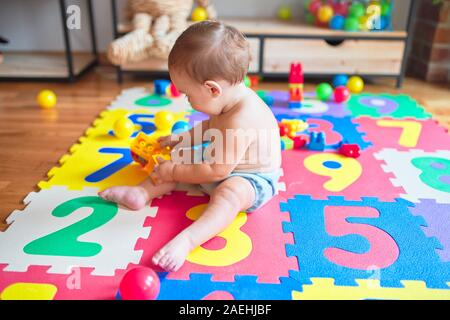 Beautiful toddler sitting on puzzle carpet playing with building blocks at kindergarten - Stock Photo