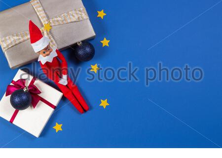 Christmas background. Toy Santa elf with Xmas present boxes on blue background. Top view - Stock Photo