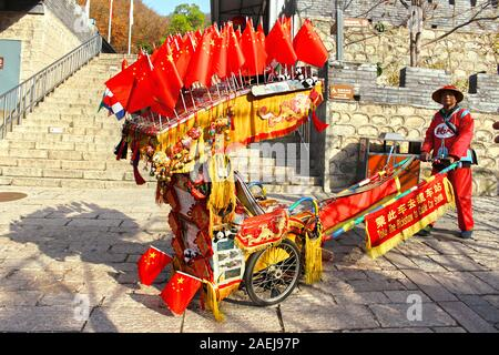 Beijing, China, November 28, 2019: Retailer or vendor wearing a traditional Chinese suit. Sign indicating to take a rickshaw to cable car station. - Stock Photo