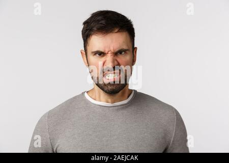 Hate, emotions and aggression concept. Hateful, furious caucasian bearded male in grey sweater, grimacing frowning look outrated and angry, grimacing