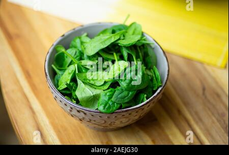 Fresh spinach leaves in a bowl on a wooden table. Eco vegan spinach salad. - Stock Photo
