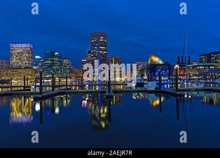 Baltimore waterfront at Inner Harbor at night, Maryland, USA. City skyline with colorful reflections in calm harbor waters. - Stock Photo