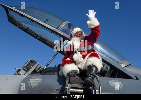 Santa Claus waves to service members and their families as he arrives in a U.S. Air Force F-16 Fighting Falcon fighter jet at McEntire Joint National Guard Base December 7, 2019 in Hopkins, South Carolina. - Stock Photo