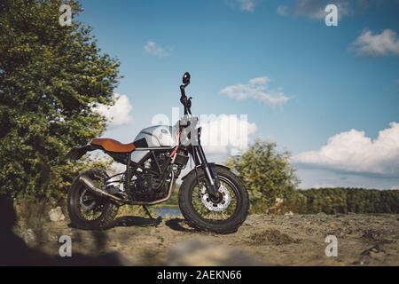 Cafe racer scrambler motorcycle, old fashioned vehicle with modern materials on forest background - Stock Photo