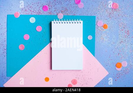 Flat lay of note pad and pencil on multicolored background with glitter and confetti. New year resolutions concept. - Stock Photo
