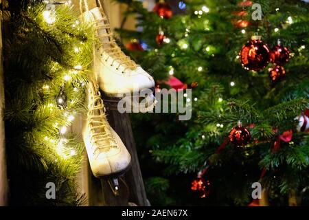 Christmas decorations on front store in European city street home. Xmas tree, red balls, ice skate, garland. Warm and cozy Christmas eve at home, wint - Stock Photo