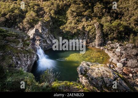 The mountain stream 'Ruisseau de Perticatu' in the Fango valley near Galeria in Corsica flows over rocks into a natural pool - Stock Photo