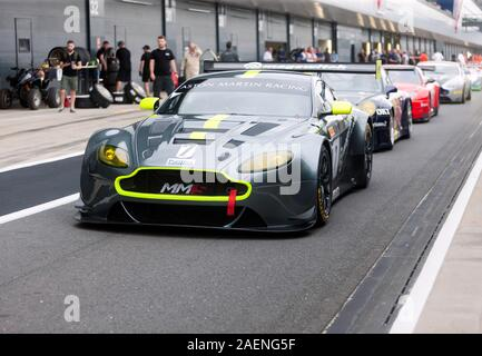 An Aston Martin Vantage V12 leads a line of Race Cars during the Aston Martin Trophy for Masters Endurance Legends, at the 2019 Silverstone Classic - Stock Photo