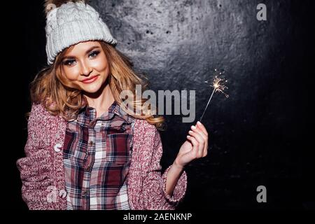 girl on holiday holding sparklers christmas tree - Stock Photo