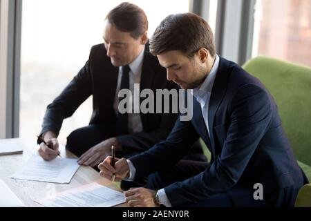Successful businessmen in suits signing contract, partnership agreement