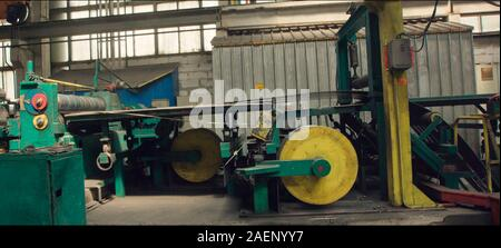 Old sheet metal cutting machine for the production of steel pipes, tubes and metal profiles in the factory. Packed rolls of steel sheet coils. - Stock Photo