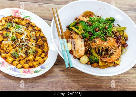 Mala Xiang Guo (stir-fry pot), and Mapo Toufu (bean curd), China Chinese Sichuan Chengdu Chongqing spicy food on table with fork spoon & chopsticks. - Stock Photo