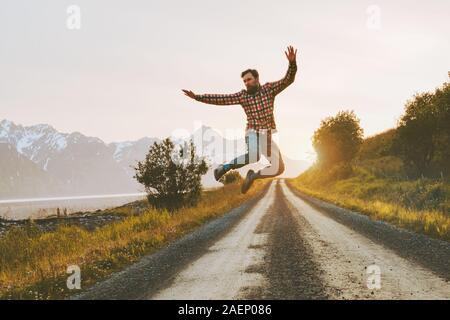 Man jumping over mountain road outdoor travel lifestyle adventure vacations activity in Norway freedom success concept happy positive vibes emotions - Stock Photo