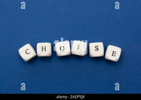 Choise word, lettering written on wooden blocks over blue background. - Stock Photo