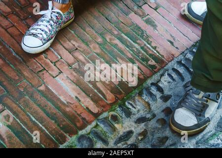 Legs of man and woman wearing in sport shoes and standing on pavement background in Italy - Stock Photo
