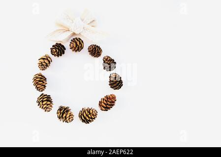 Beautiful eco friendly Christmas wreath made with pine cones and cotton ribbon on white background. Creative festive garland, top view, minimal style. - Stock Photo