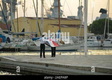 Descent of the national flag at sunset at the naval base of Toulon Var France - Stock Photo