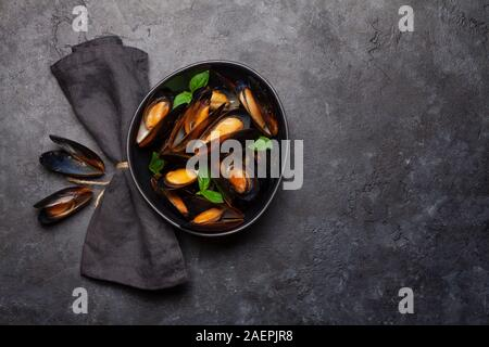 Mussels in tomato sauce and basil leaves. Top view flat lay with copy space - Stock Photo