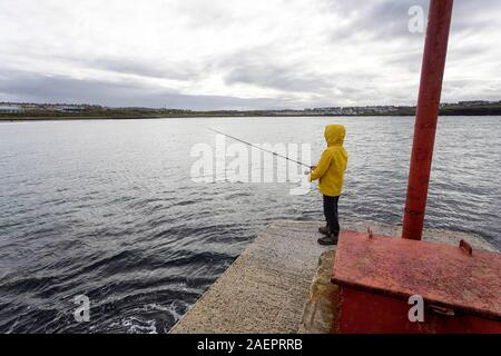 Young boy in yellow jacket fishing in  the arbour, Portrush, County Antrim, Ulster, Northern Ireland, Europe - Stock Photo