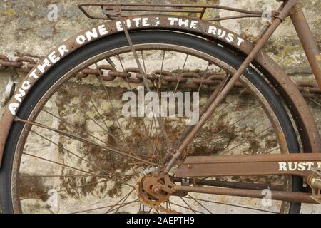 An old rusty bicycle chained to a wall in Paris.Rust in peace in written on the side of it. - Stock Photo