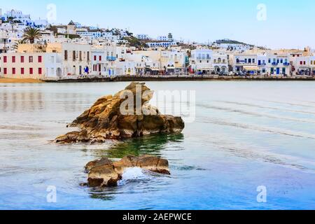 Mykonos, Greece - April 23, 2019: Famous island white houses, promenade, beach, view from the sea in Cyclades