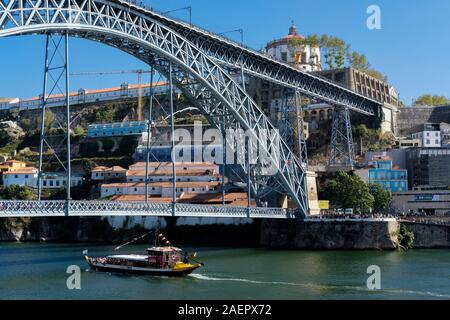 A Barco Rabello - trip boat - on the Rio Douro passes under the Ponte de Dom Luis I, between the city of Porto, and Gaia, Portugal. - Stock Photo
