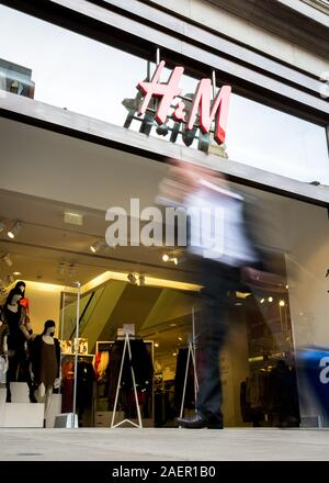 H&M clothes store. Blurred shoppers walking past the shop front to the H&M shop, a fashion retailer, on London's Oxford Street.