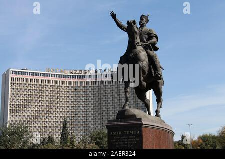Amir Temur statue and Soviet era Uzbekistan Hotel in Tashkent - Stock Photo