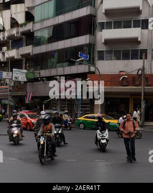 An electric scooter rider defies road safety logic on a busy junction in Bangkok with motorbikes, taxis and cars around him on the bend, Thailand - Stock Photo