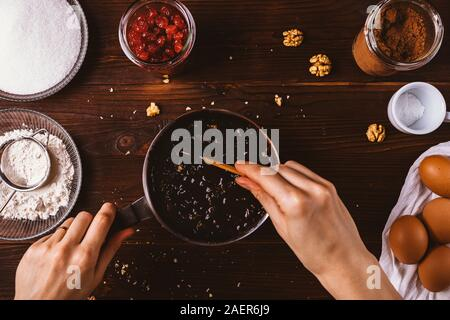 Female's hand mix melted chocolate with chopped walnuts in saucepan among other ingredients on dark wooden table. Top view process of making dough for - Stock Photo