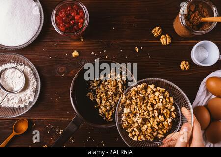 Woman's hand adding chopped walnuts into melted chocolate in saucepan among ingredients for baking brownie cake on rustic background, top view. - Stock Photo
