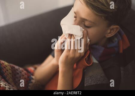 Sick boy with cold rhinitis sits with woolen blanket and hot water bottle. Sad teen with the flu blow his nose with napkin. Child with seasonal infect - Stock Photo
