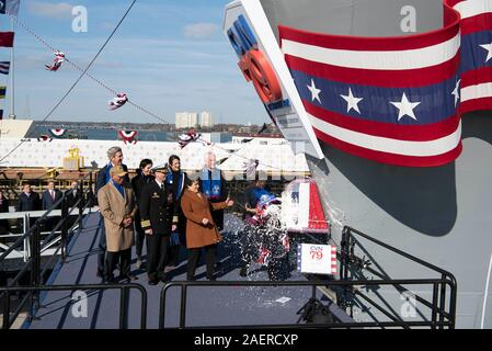 Amb. Caroline Kennedy, right, daughter of the late President John F. Kennedy swings a bottle of champagne to christen the new Ford-class aircraft carrier USS John F. Kennedy at Huntington Ingalls Industries December 7, 2019 in Newport News, Virginia. Kennedy is the second ship in the next-generation Ford-class of nuclear-powered aircraft carriers and the second U.S. aircraft carrier named for President Kennedy, with the former retired from service in 2007. - Stock Photo
