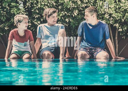 Young male enjoying days off of school relaxing in the swimming pool. Smiling teenagers sitting on the edge of the pool. Happy people enjoy summer - Stock Photo