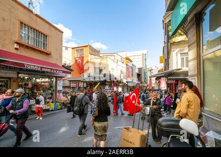 Local Turks shopping the large Eminonu outdoor market bazaar as they walk near a flying Turkish Flag in Istanbul, Turkey - Stock Photo