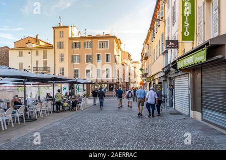 Local French enjoy breakfast at an outdoor sidewalk cafe near the outdoor flea market in the seaside town of Antibes, France, on the French Riviera. - Stock Photo