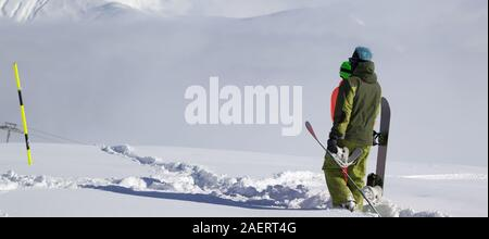 Snowboarders on snowy off-piste slope with new fallen snow at winter day. Panoramic view. - Stock Photo