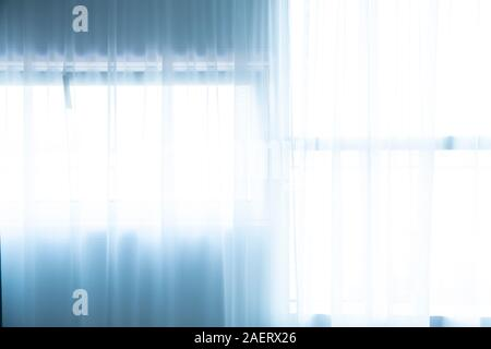 Light falls through windows, with curtains, into a room, - Stock Photo