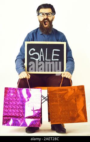 Bearded man, long beard. Brutal caucasian angry hipster with moustache in glasses holding colorful shopping packages, sale inscription on blackboard, sitting on chair isolated on white background - Stock Photo