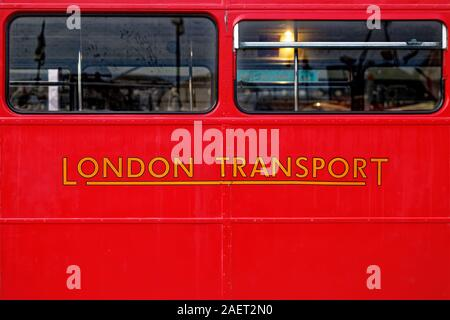 Yellow colored London Transport text written below windows of a red vintage double decker bus in Rahmi M. Koc Museum in Istanbul. - Stock Photo