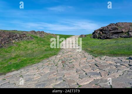 A path made of stone cobblestones leading to the top of the mountain against a blue sky. - Stock Photo