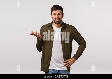 Man having complain, arguing with business partner. Displeased and annoyed, aggressive bearded man raise one hand frustrated and puzzled, stare - Stock Photo
