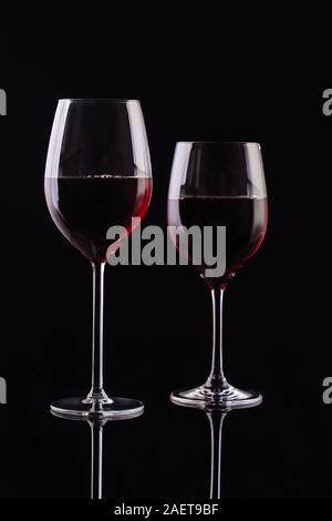Two glasses with red wine on a black background. Wine on the dark - Stock Photo