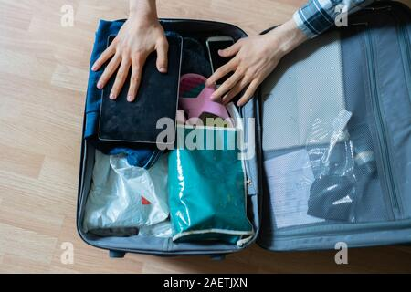 the overhead top view of person packing the bag with his personal things on the wooden florr at home - Stock Photo