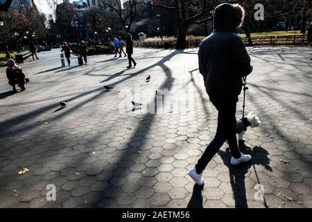 Pedestrians walk through Washington Square, NYC, in winter light. - Stock Photo