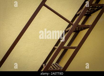 Side view of the steel staircase attached to the wall on the building exterior - Stock Photo